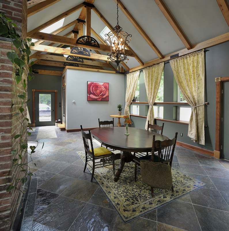 The dining room boasts a cathedral ceiling, wooden beams, skylights and a slate floor.