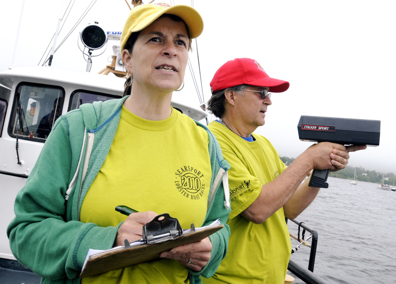 Race officials Patty and Jim LeClair watch from the Coast Guard boat as racers cross the finish line. The family owns and operates the Maine Coast Welcome Center in Belfast.