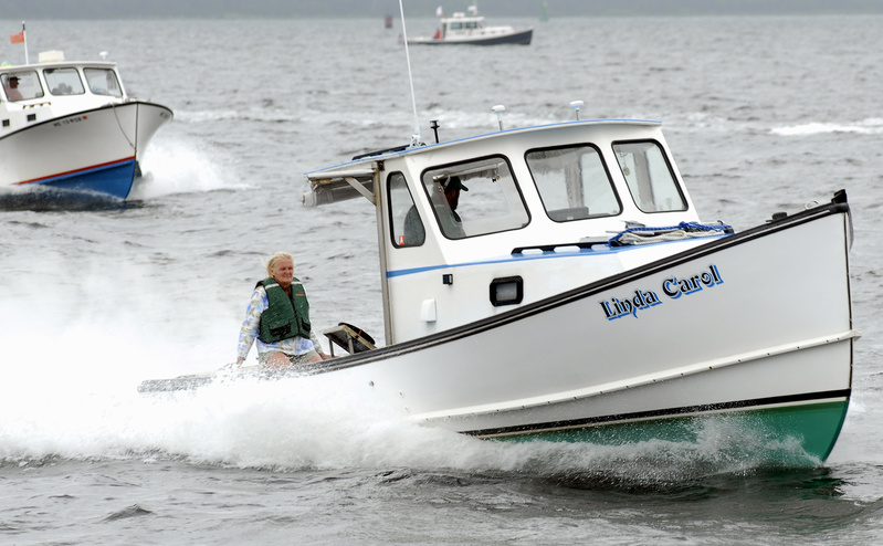 Linda Smith sits tight as the Linda Carol races to victory in the Gasoline Class B race during the recent lobster boat series event in Searsport. The boat, operated by Chris and Linda Smith, also finished second in the Gasoline Free for All. Lobster boat racing can be described as a block party on water.