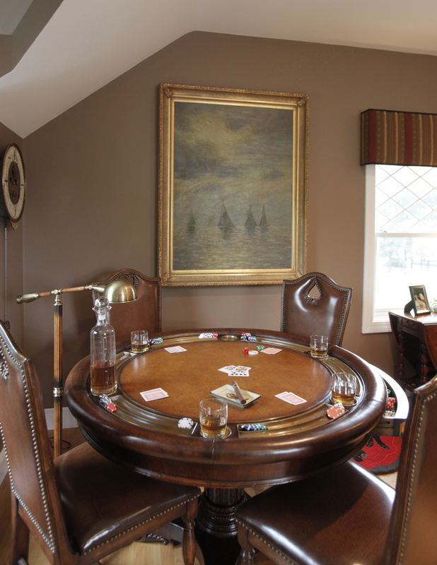A round poker table with side chairs makes good use of a corner area in a room designed by American Traditions of Portsmouth, N.H.
