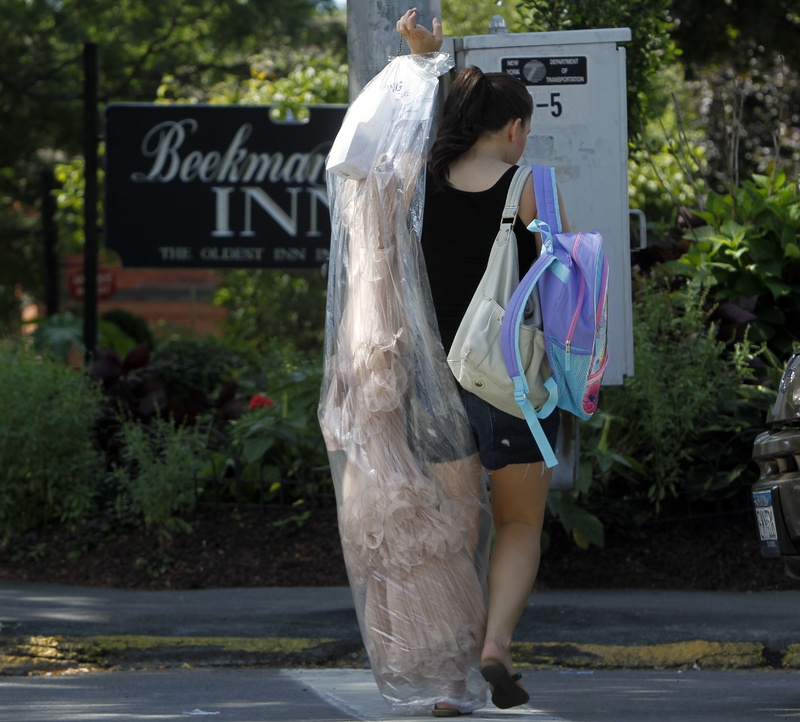 A woman carries a gown outside the Beekman Arms Inn in Rhinebeck, N.Y., today. Chelsea Clinton and fiance Marc Mezvinsky are expected to be married in Rhinebeck tonight.