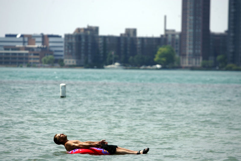 Stefan Sidorowicz, 43, of Hamtramck, Mich., floats along the Detroit River off Belle Isle as temperatures climbed above the mid-'90s in Detroit on Monday.