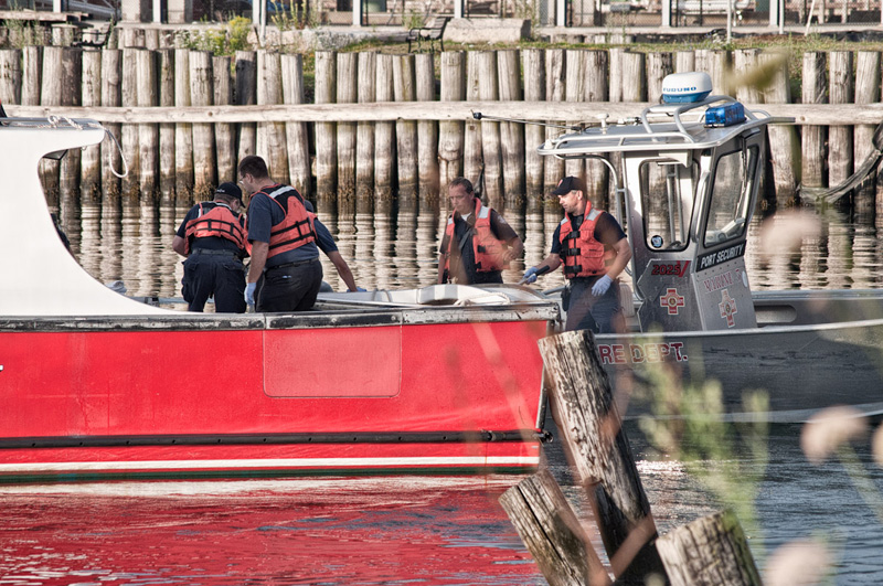 Portland firefighters recover a body from the harbor this morning.