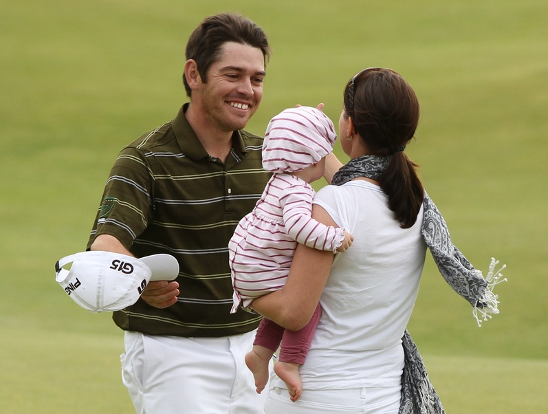 South Africa's Louis Oosthuizen celebrates on the 18th green with his wife Nel-Mare and baby after winning the British Open Golf Championship on the Old Course at St. Andrews, Scotland today