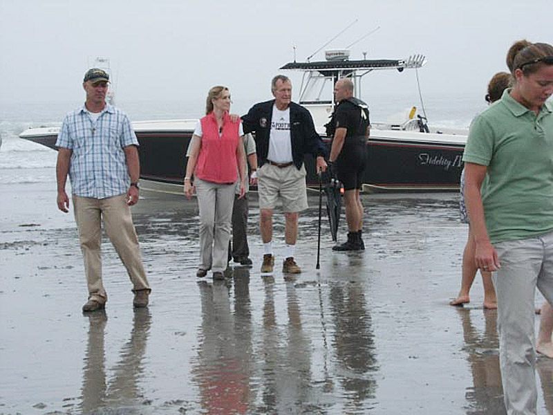 Former President George H.W. Bush and some family members walk away from The Fidelity IV as it sits stranded on Gooch's Beach. Hours later, his staff moved the boat to its dock in Kennebunkport.