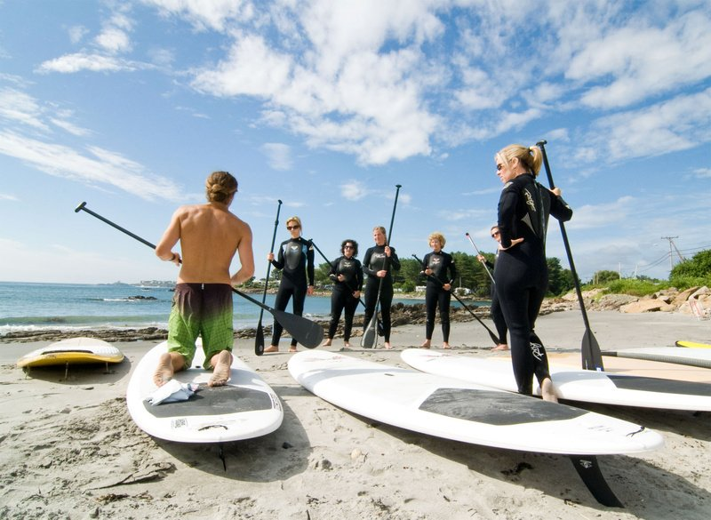 Nico Evans, an instructor with Liquid Dreams Surf Shop in York, kneels as he instructs a class on foot positioning before heading into Cape Neddick Harbor to stand-up paddle.