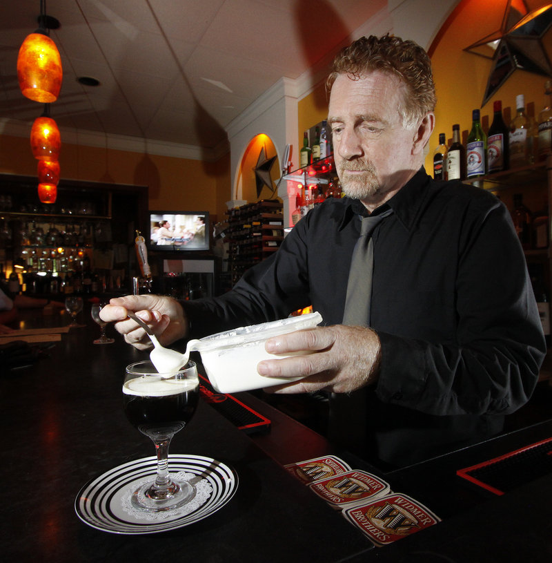 Johnny Robinson, proprietor of Johnny's Bistro & Bar in Falmouth – and part of its authentic charm – tops off an Irish coffee with lightly whipped cream.