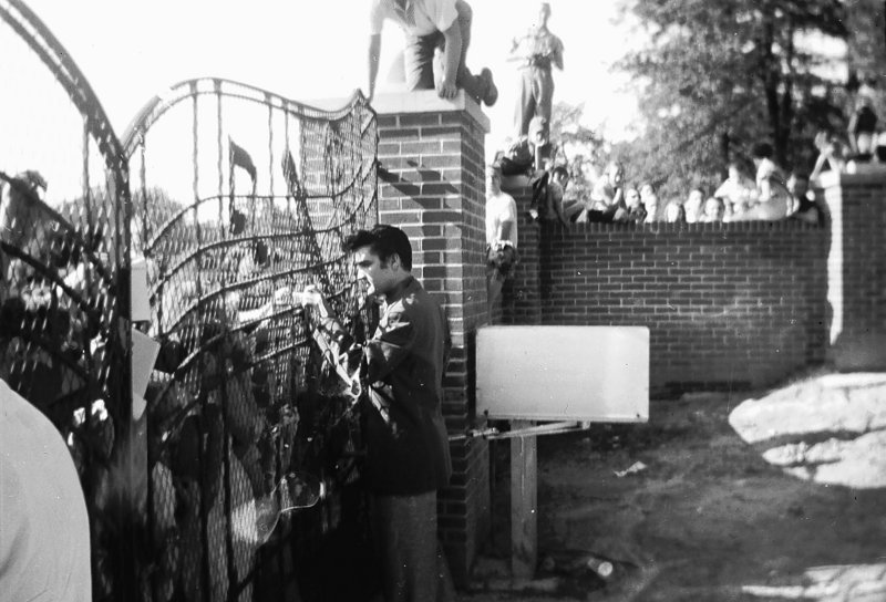 Elvis Presley greets fans at the gates of Graceland in Memphis, Tenn., in 1957 in this previously unpublished photo.
