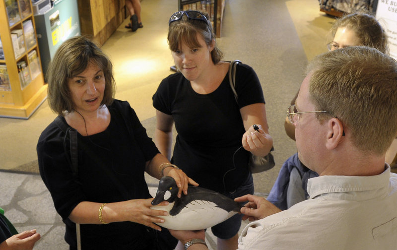 Susan Shapiro, left, of Port Washington, N.Y., one of the volunteers in the interpreting program, is blind and hard of hearing. Student Rachel Morrison holds a small microphone connected to Shapiro's amplified hearing system so she can understand as Jason Ohman, right, of Bean's hunting and fishing department, talks about the wooden decoy she is feeling.