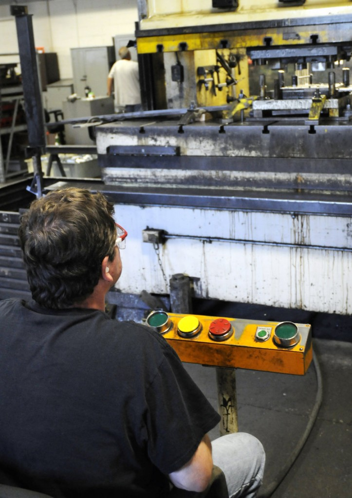 Kevin Hobart, left, operates a 200-ton press that stamps and forms metal components.