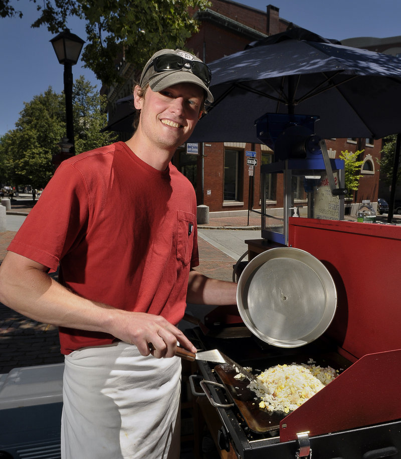 Ben O'Connell heats a special rice dish at the Bazkari lunch cart on Free Street in Portland.