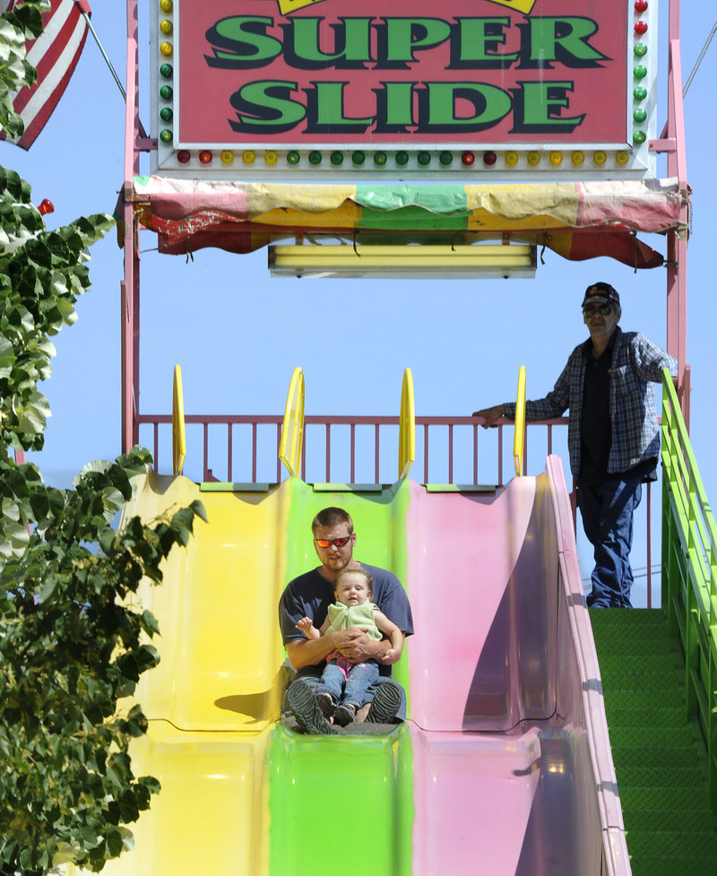 Garret Mathews and his 19-month-old daughter Kayla of Bath try the Super Slide. The festivities culminate in fireworks over the Kennebec River on Monday night.