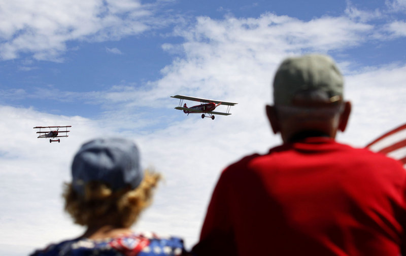 Ruby Barnes of Vassalboro, left, and Claud Daigle of Winslow watch as two Fokker airplanes approach the viewing area. The plane on the right is an original 1923 Fokker C.IV; the one on the left is a 1917 Fokker DR.I reproduction.