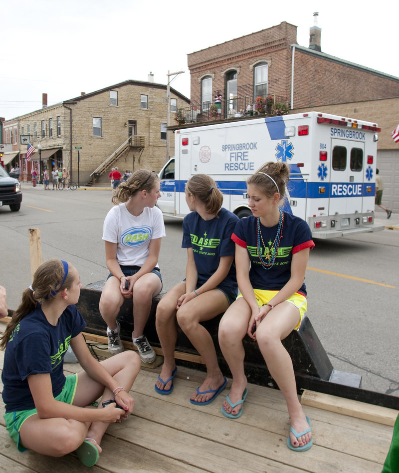 Parade-goers sitting on a float watch an ambulance pass after two horses trampled people at a Fourth of July parade in Bellevue, Iowa, Sunday. A 60-year-old woman later died.