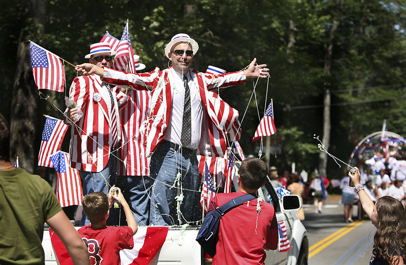 Ocean Park Barbershop Quartet member Mark Andrews gets sprayed with Silly String by his friends Calvin Reddington, left, Andrew Dudley, middle, and Hannah Lanoue, far right, at the conclusion of the 60th annual Independence Day Community Parade in Ocean Park on Monday.
