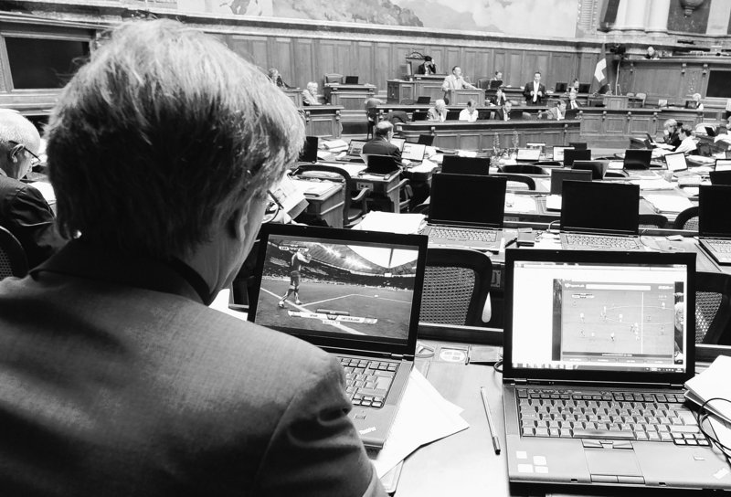 Swiss lawmaker Claude Ruey watches the World Cup soccer match between Spain and Switzerland during a debate in Parliament on June 16. The World Cup only comes around for a month every four years, and there's no way to keep fans from watching – even during work. Many bosses allow it so they can watch as well.