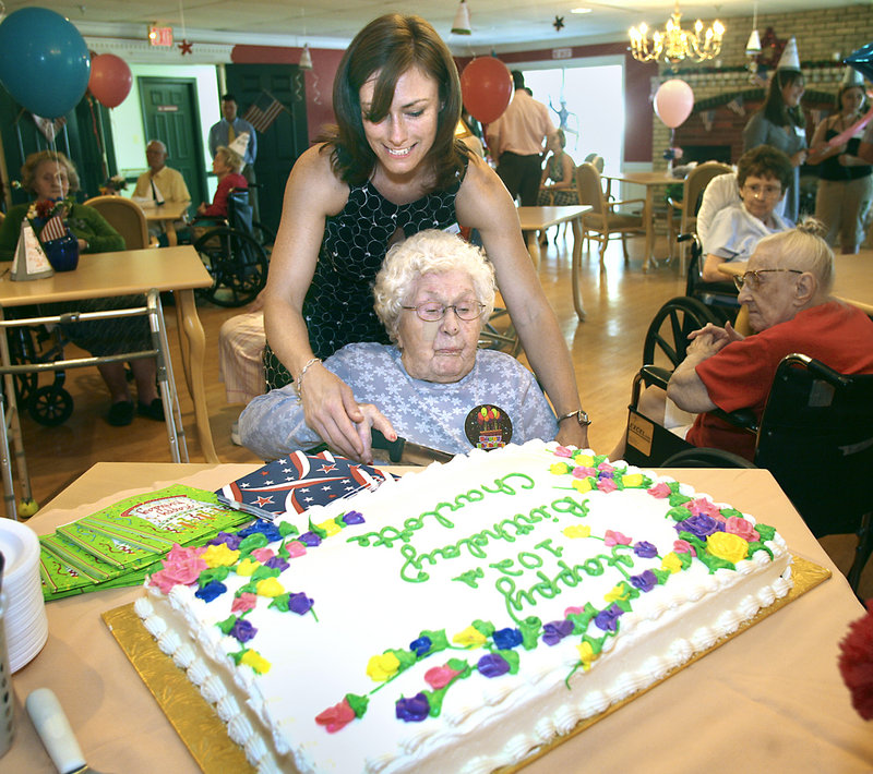 Charlotte Farrin, 102, cuts her birthday cake with the help of Mandy Johnson, director of recreational therapy at Evergreen Manor in Saco, during Farrin's party on Monday.