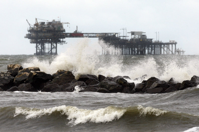 An oil rig is seen beyond a jetty at Fourchon Beach in Port Fourchon, La., on Monday. Despite extensive study by a host of experts, it has been hard to get a handle on just how much ecological damage the BP spill has caused in the Gulf of Mexico.