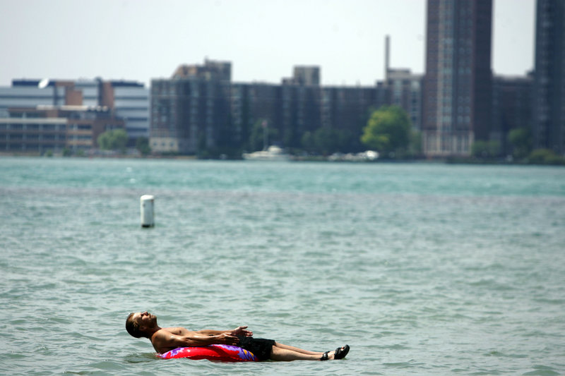 Stefan Sidorowicz, 43, of Hamtramck, Mich., floats along the Detroit River off Belle Isle as temperatures climbed above the mid-90s in Detroit on Monday.