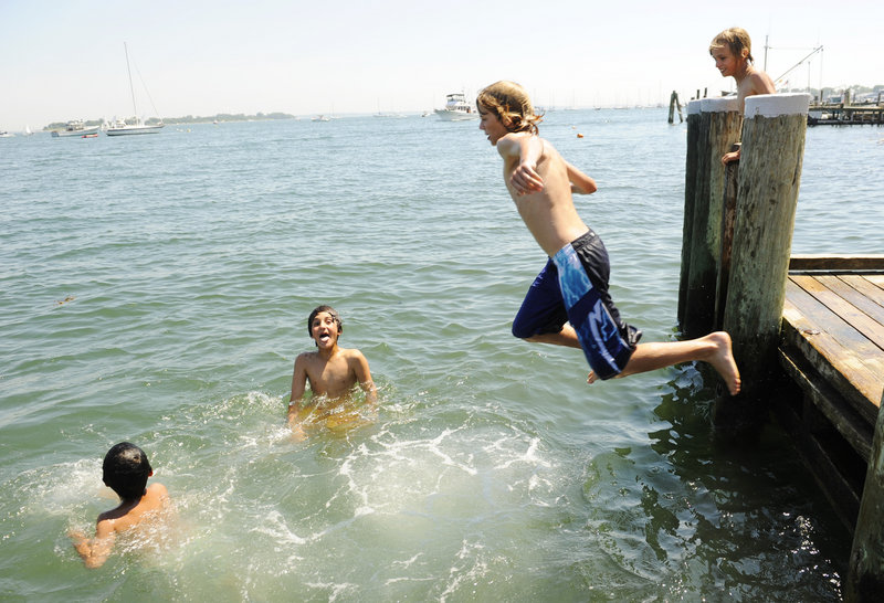 Kamal Kalkhoran, 8, far left, and his brother Kameal, 11, second from left, tread water as Greg Cooper, 12, dives into the Mystic River as Jonathan Cooper, 9, looks on from the Main Street dock in the Groton, Conn., village of Noank, on Monday, July 5, 2010. A string of hot days were expected this week, with temperatures en route to 100-plus degrees in some places. Temperatures reached into at least the 90s Monday from Maine to Texas, into the Southwest and Death Valley. (AP Photo/The Day, Sean D. Elliot) MANDATORY CREDIT; MAGS OUT; INTERNET OUT; NO SALESAP Photo/The Day, Sean D. Elliot