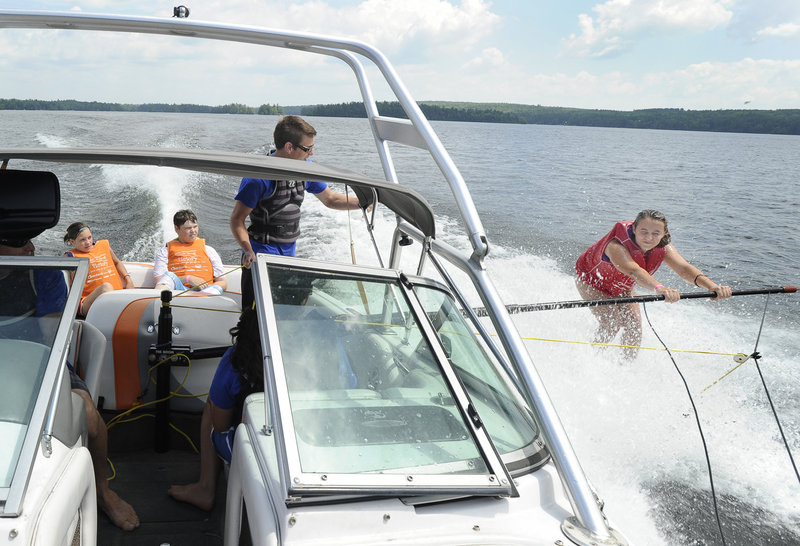 Aria Kneeland, 13, of Windham, skis alongside the In His Wakes program's boat Tuesday as Jake Miller provides instruction on Little Sebago Lake in Windham.