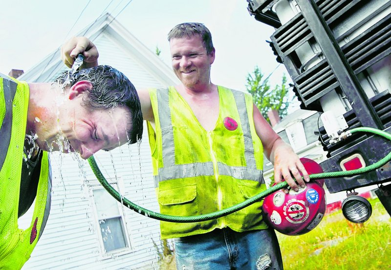 Mike Melanson helps Andrew Eaton cool off during a break with Shaw Brothers Construction in South Portland on Tuesday.