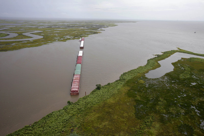 Barges are lined up Tuesday to block oil from the BP spill from flowing through Chef Menteur Pass, which connects the Gulf of Mexico to Lake Pontchartrain. Tar balls from the spill infiltrated the lake last weekend.
