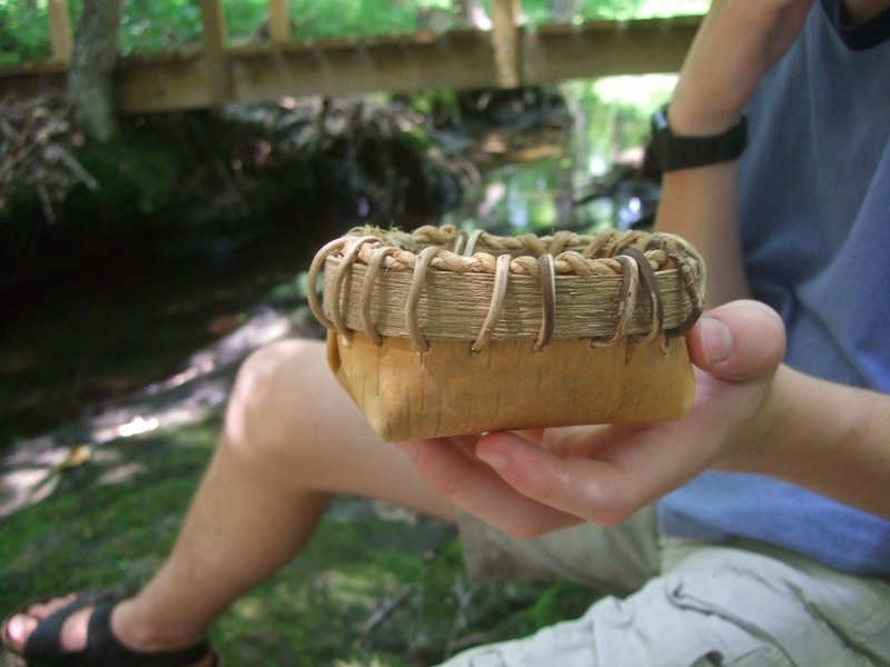 Desmond Molloy holds out his finished birch bark basket.