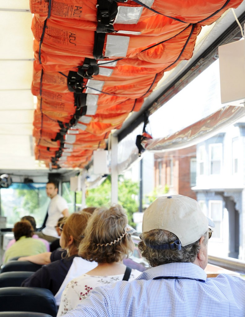 Downeast Duck Adventures passengers sit beneath life vests strapped to the ceiling. The tour of Portland sights takes place on a custom-built amphibious craft.