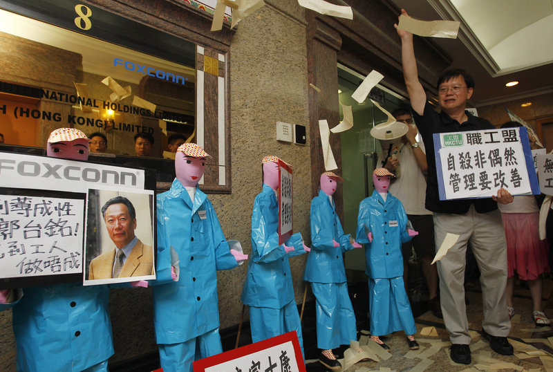 Labor activists throw paper money near figures representing deceased workers at Foxconn Technology Group in Hong Kong. Demands for better wages and working conditions are hastening the eventual end of cheap labor costs in China.