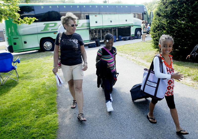 From left, volunteer host mom Barbara Judge of Portland walks with Nadia Grey and Kristina Perez after the Fresh Air Fund kids got off the bus from New York City at Wentworth Intermediate School in Scarborough on Thursday. Maine has 25 host families this summer, all of whom went through an extensive vetting process, coordinators for the fund say.