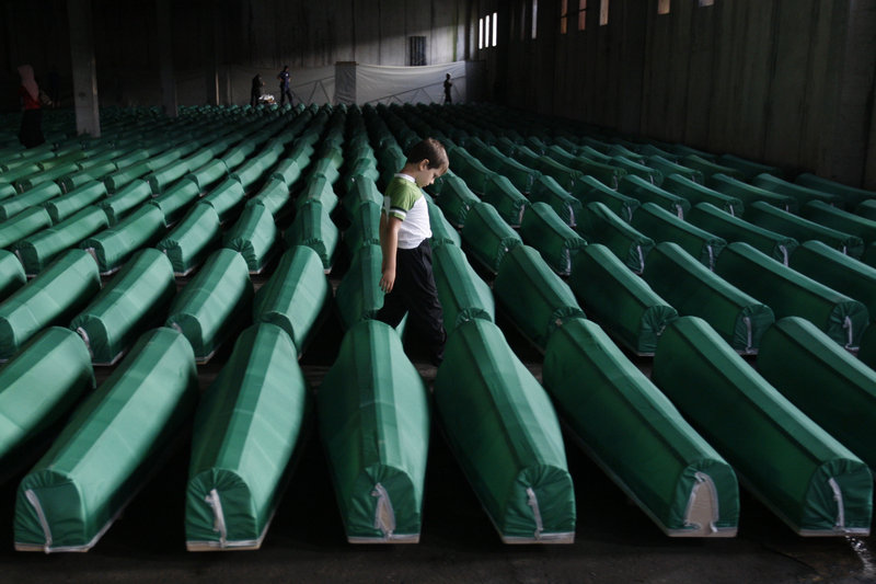 A Bosnian Muslim boy walks among coffins of Srebrenica victims at the memorial center at Potocari near Srebrenica on Friday. Bosnian Serb troops massacred up to 8,000 Bosnian Muslim men after capturing Srebrenica on July 11, 1995.