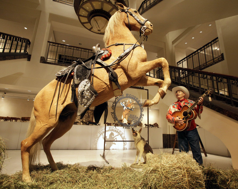 Gil Perez, a doorman at Christie's, wears a Roy Rogers outfit and holds a guitar that belonged to Rogers as he stands next to the preserved remains of Rogers' horse Trigger and dog Bullet during an auction preview in New York on Friday.