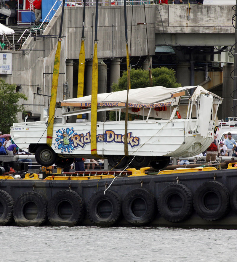 The amphibious duck boat that had stalled and was then sunk by a barge is lifted by a crane from the Delaware River in Philadelphia on Friday. Two died in the accident.