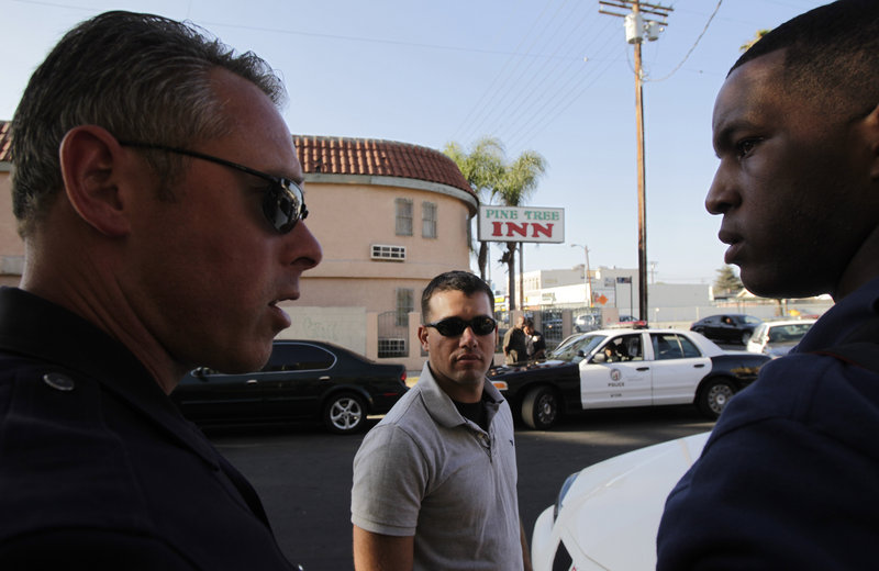 Camp Pendleton Marine Lt. Andrew Abbott, center, and Cpl. Warren Burton, right, listen to Los Angeles police Sgt. Arno Clair during a drug bust in Los Angeles. Abbott is one of 70 Marines who recently patrolled streets with the Los Angeles Police Department for a week.