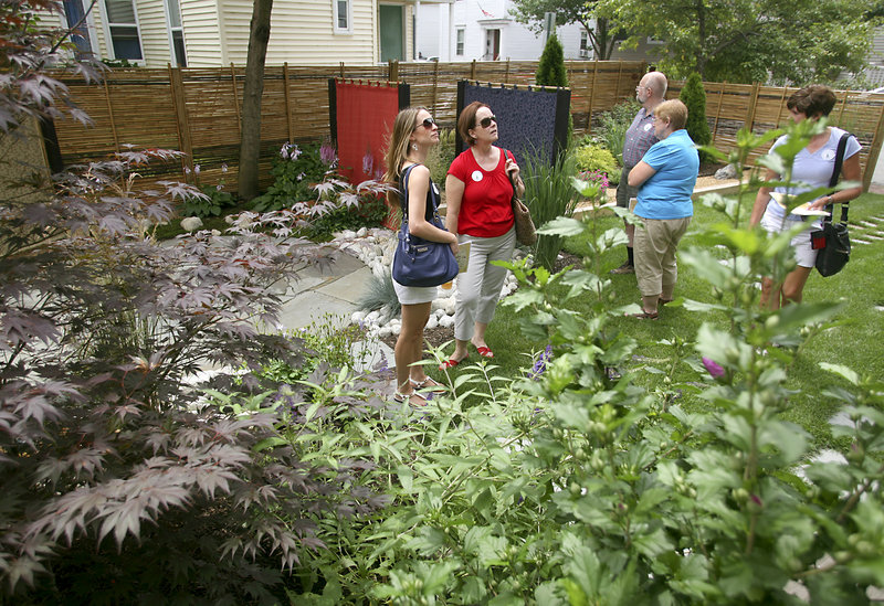 Visitors view the Japanese garden at 59 Lafayette St. The garden was created to provide a peaceful yet energizing landscape..