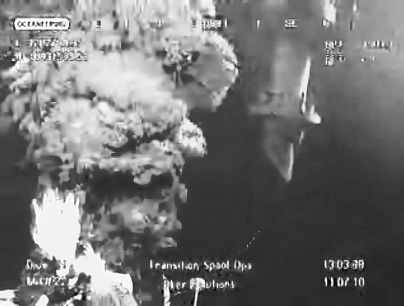 In this image taken from video provided by BP PLC, oil leaks from the fractured wellhead, left, as the transition spool, right, which will go into the gushing wellhead before the new containment cap is placed on, is maneuvered above at the site of the Deepwater Horizon oil spill in the Gulf of Mexico on Sunday.