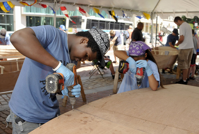 Steeve Francois, 18, of Haiti, screws the bottom plank to the 12-foot Bevins skiff he was helping to build Monday.