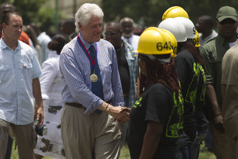 Bill Clinton, U.N. special envoy for Haiti, center, greets reconstruction workers during a service for the six-month anniversary of the Jan. 12 earthquake in Port-au-Prince.