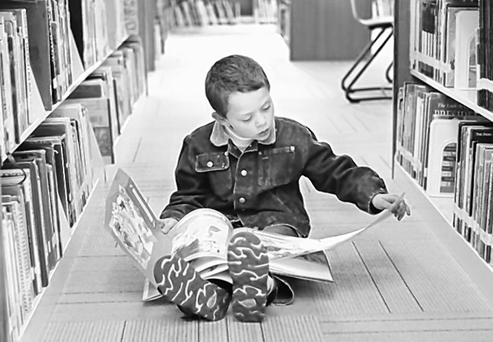 Elijah De Gouveia, 5, of Standish reads a book in the new children's area of the Portland Public Library.