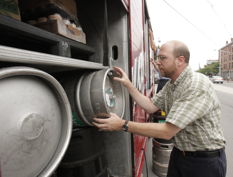 Reporter Ray Routhier puts an empty keg back on a National Distributors truck while delivering beer and wine in Portland.