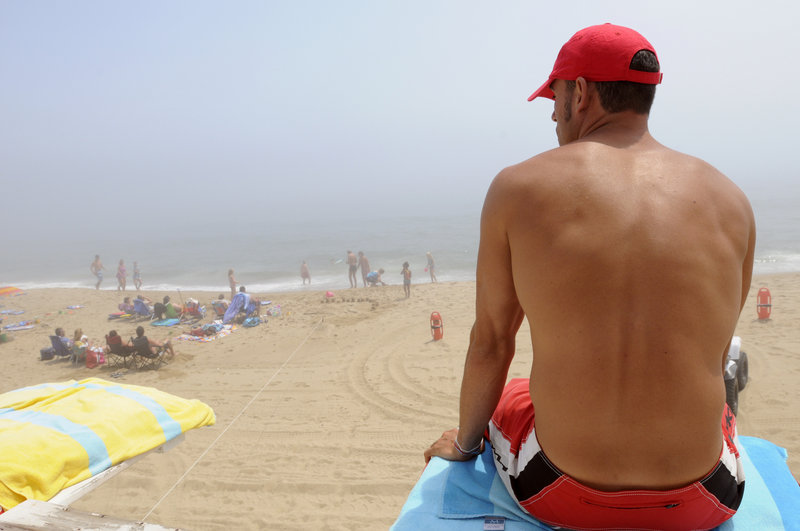 Lifeguard Lance Timberlake watches visitors to Old Orchard Beach from a guard tower Tuesday. On Sunday and Monday alone, lifeguards reported 49 incidents in which they had to assist people caught in riptides there. In a more typical week, there are only a few incidents daily.