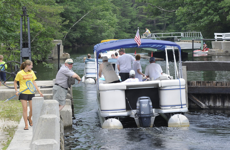 Inspector Kelly Baldwin checks a boat for milfoil Tuesday as it passes through the Songo Locks in Naples. Inspectors will urge boaters to stay out of the Songo River to prevent milfoil from re-entering Brandy Pond and waters to the north.