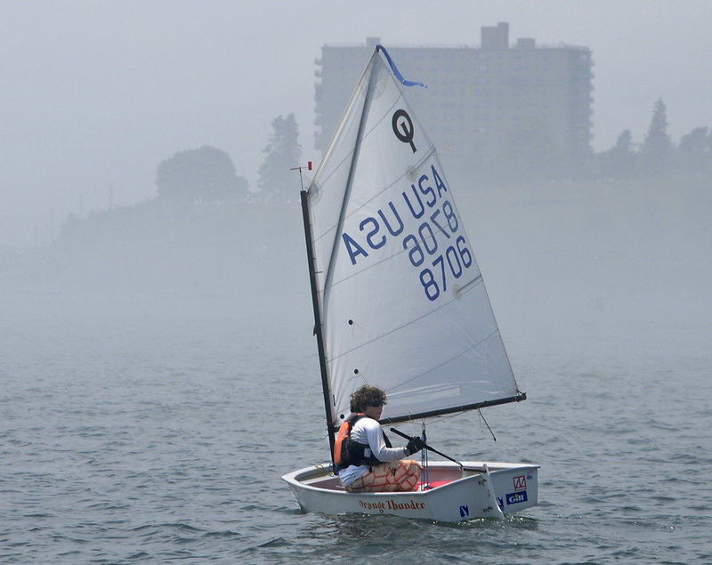 Cooper Slepert of the Portland Yacht Club waits out a fog Tuesday off the Eastern Promenade in Portland as the two-day USA Junior Olympic Sailing Festival Northeast championships began.