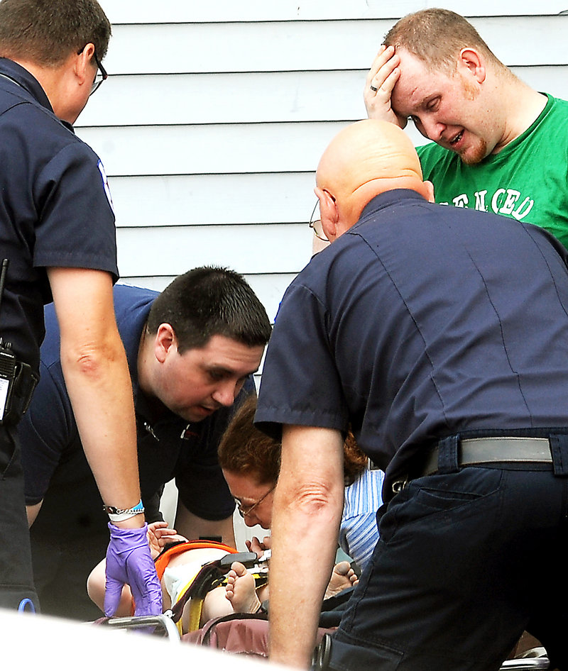 The mother and father of a 22-month-old boy who fell from the third floor of their apartment at 21 Walnut St. in Lewiston, react as their child is about to be loaded by emergency personnel into an ambulance on Tuesday morning. Police said the child had landed in a pile of soft dirt and was conscious when he was taken to Central Maine Medical Center in Lewiston.