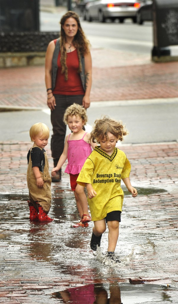 Wyatt Bicycle Kennedy splashes through rain puddles in Portland's Monument Square on Wednesday afternoon while he's watched by his mother, Nicole Niehoff (rear) and friends Seamus Clermont and Amina Edgewood Writer.