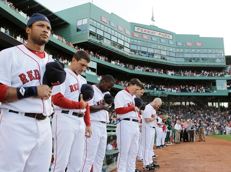Members of the Boston Red Sox pause for a moment of silence before Thursday's game to honor George Steinbrenner, the Yankees' owner, and Bob Sheppard, the Yankees' public address announcer. Both died this week.