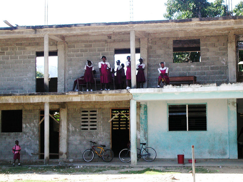 Children stand on the second floor of a school under construction in Haiti that has lacked a roof, doors, windows and second-floor safety railings for about a decade.