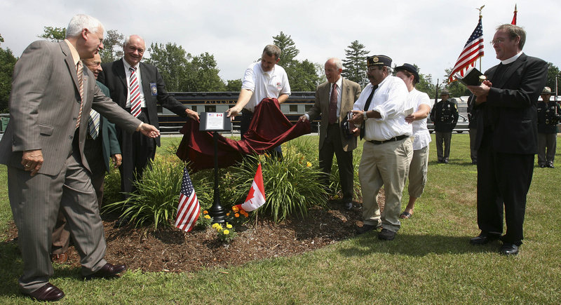 A plaque about the memorial is unveiled at the ceremony.