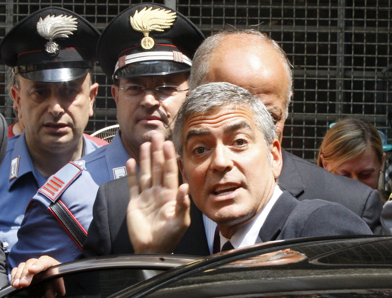 George Clooney waves at a tribunal in Milan, Italy, Friday. The actor was a witness in a fraud trial charging three men with co-opting his name for a line of clothing.
